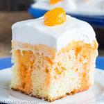 piece of orange creamsicle poke cake on a plate