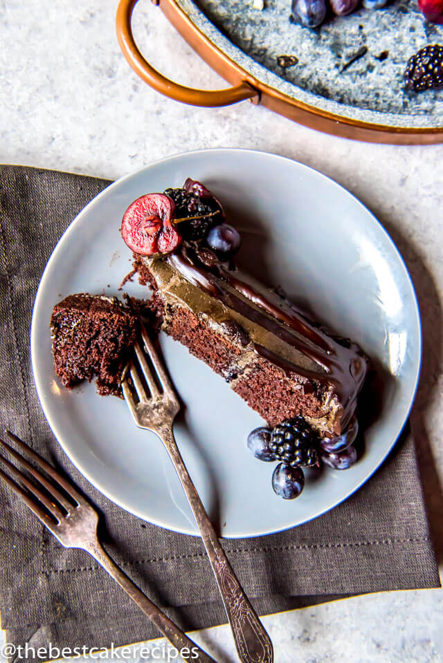 A piece of cake on a plate, with Chocolate and Blackberry