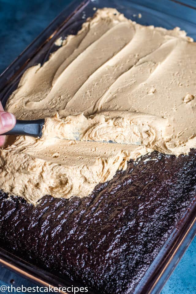 knife spreading peanut butter frosting on a chocolate cake