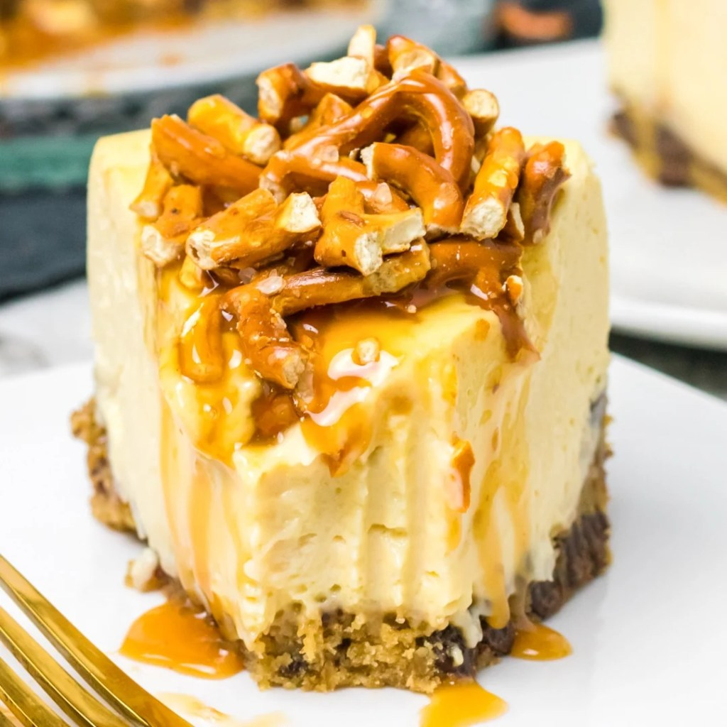 Caramel Pretzel Cheesecake on a plate with a bite out