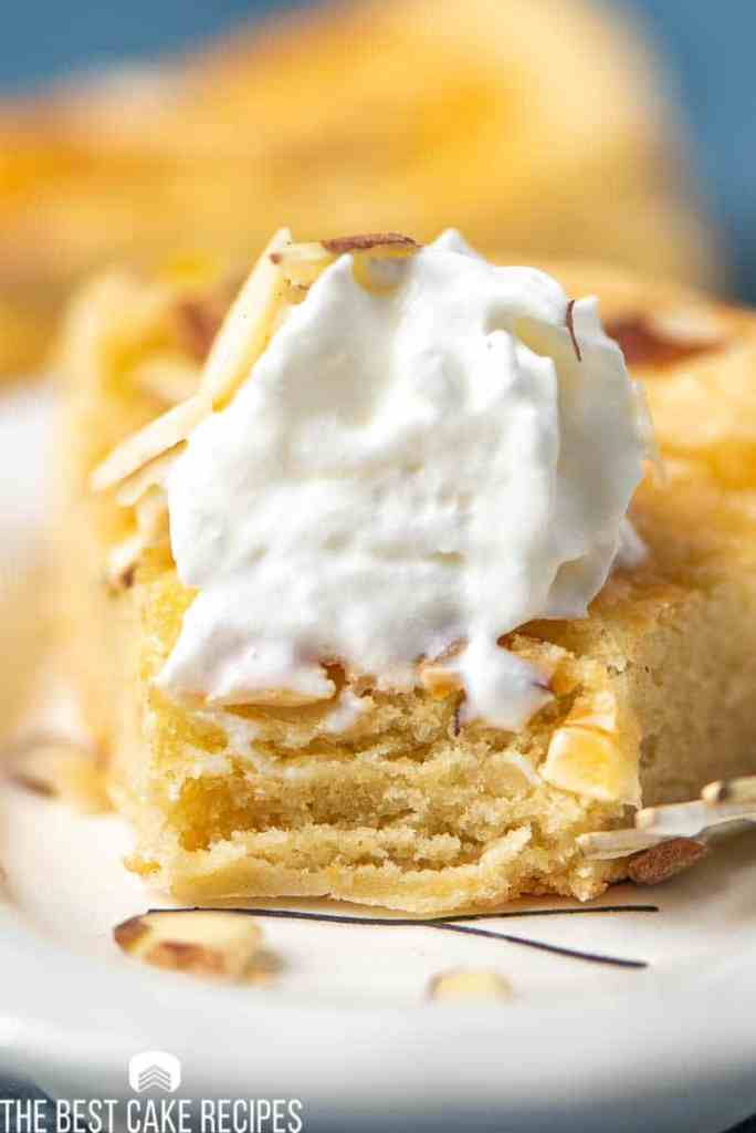closeup of dutch butter cake  on a plate with whipped cream and bite out of it