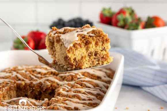 piece of coffee cake on a spatula with fruit in the background