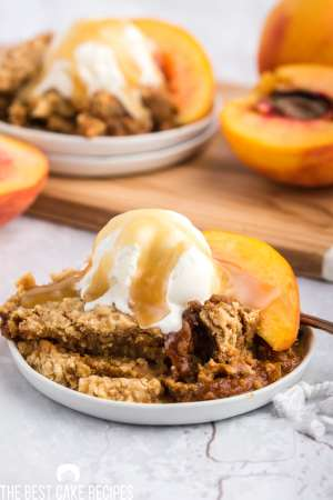 slow cooker peaches and cream cake a la mode on a plate