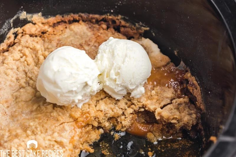 peach dump cake with ice cream in a slow cooker