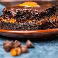 slice of caramel chocolate turtle cake on a plate with a bite out