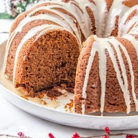 close up of gingerbread bundt cake on a plate with one slice out