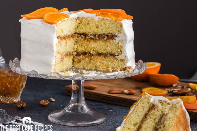 orange cake on a cake stand with one piece plated