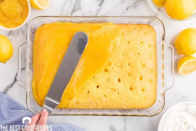 spreading lemon curd on a poke cake