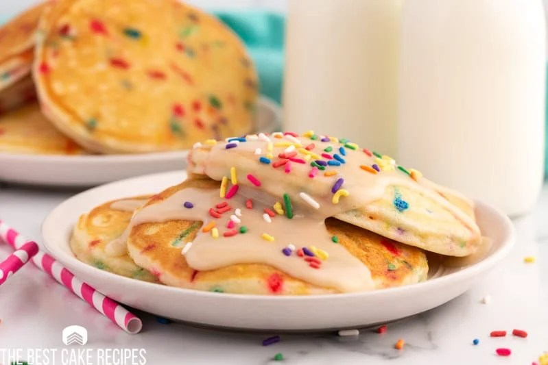 3 funfetti pancakes on a plate with icing