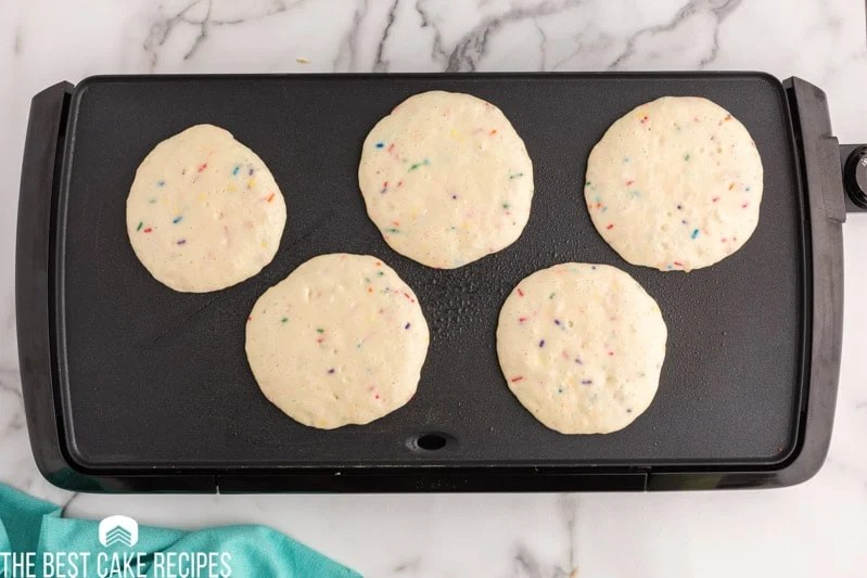 5 uncooked pancakes on a griddle