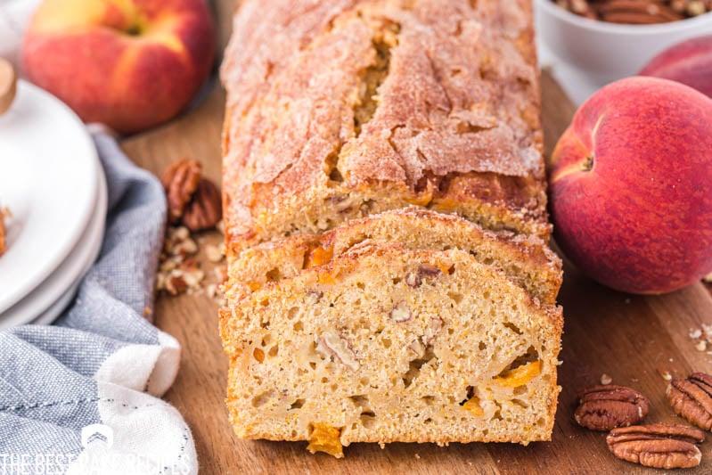 a loaf of peach loaf cake on a cutting board