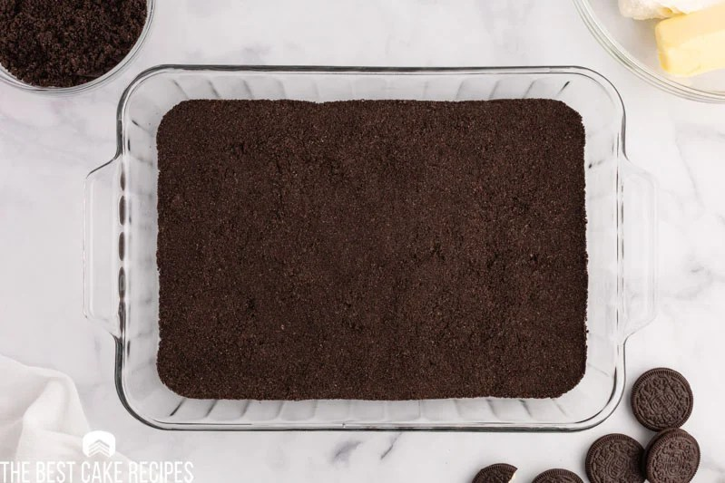 crushed oreo cookies in the bottom of a baking pan