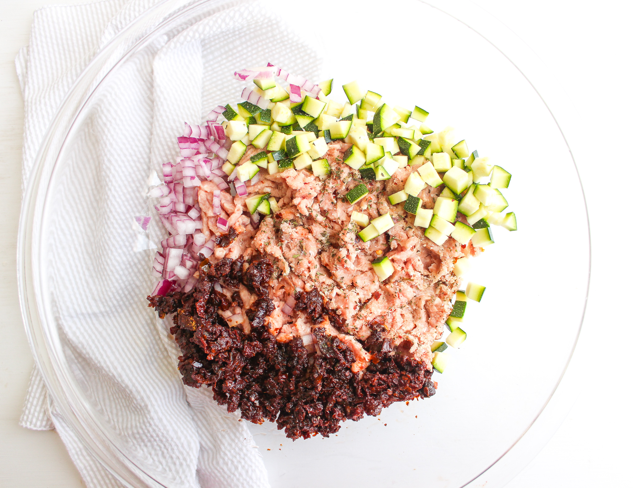 Bowl of ground turkey, diced red onion, diced zucchini, and chopped sun-dried tomatoes