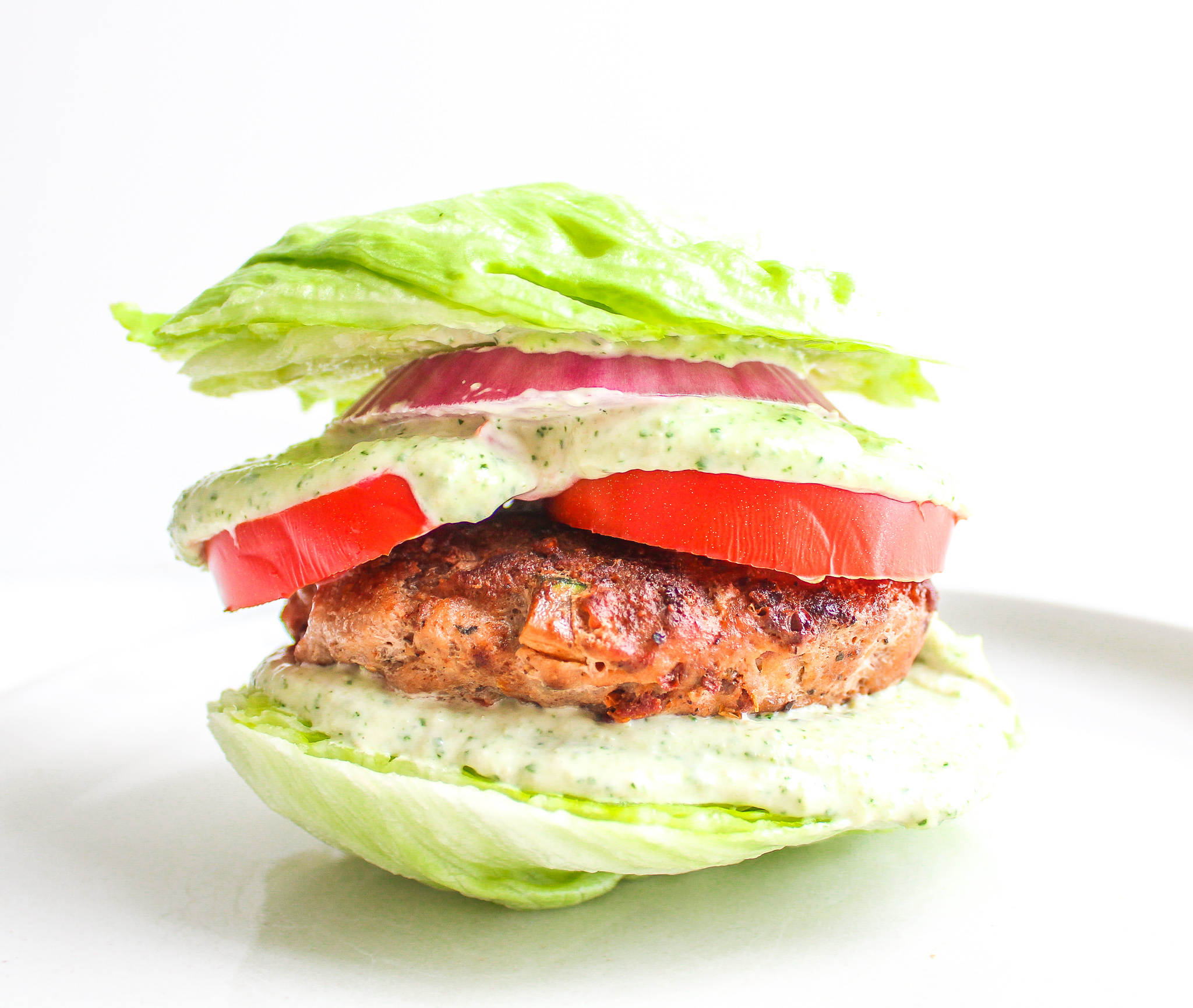 Greek Turkey Burger on a lettuce bun with thick tomato slices, red onion and pesto aioli