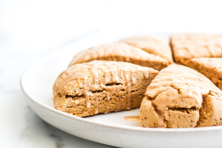 Gluten Free Cinnamon Scones with Maple Icing dripping down the sides on a white serving plate
