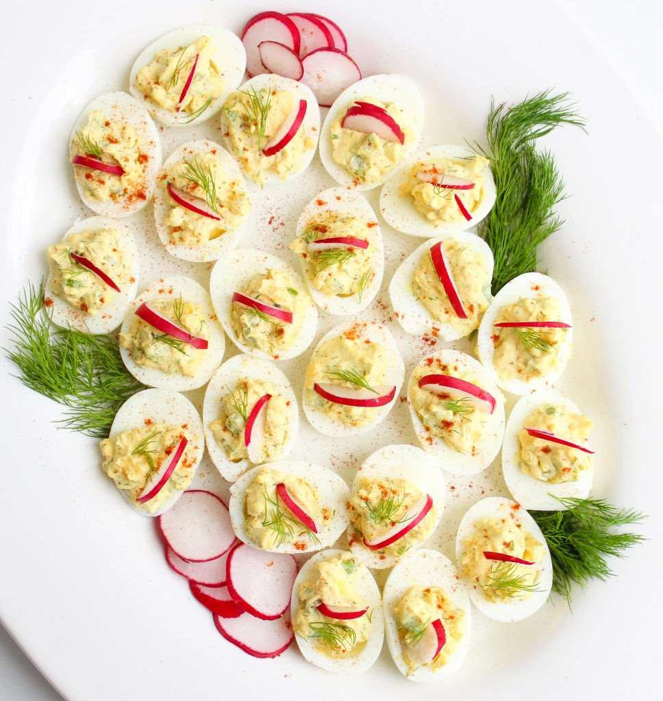 Deviled Eggs topped with sliced Radishes and fresh Dill on a white serving platter with radish slices and dill all around it