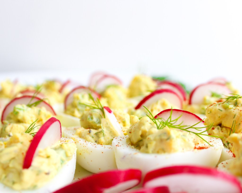 Deviled Eggs topped with sliced Radishes and fresh Dill