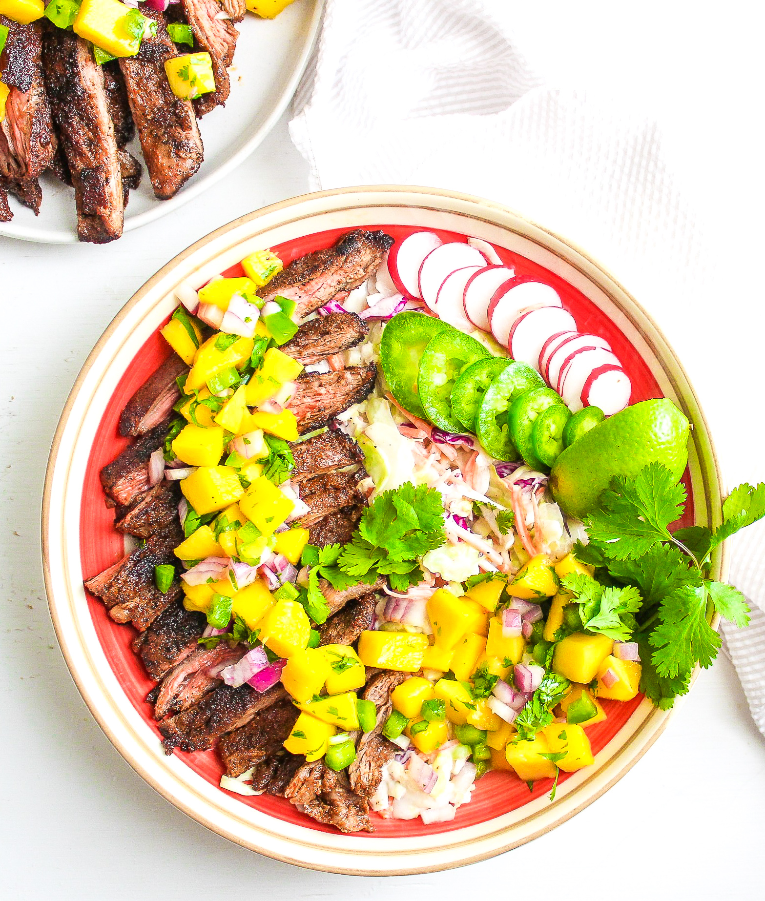 Sliced steak over coleslaw, topped with fresh mango salsa