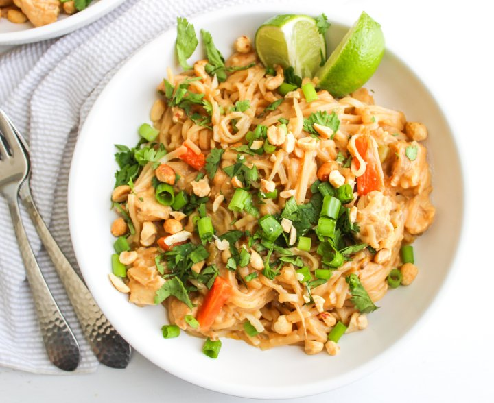Instant Pot Pad Thai in a white bowl topped with cilantro and served with lime wedges