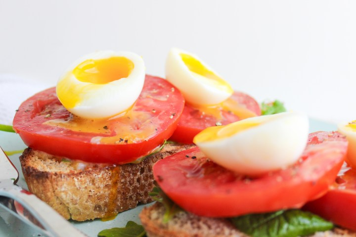 Sourdough toast topped with fresh greens, tomato slices and jammy eggs with the yolks running down
