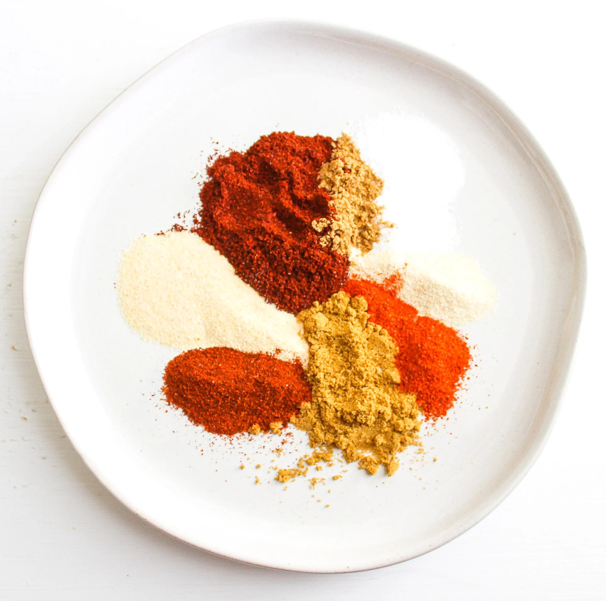 Assortment of herbs and spices on a white plate