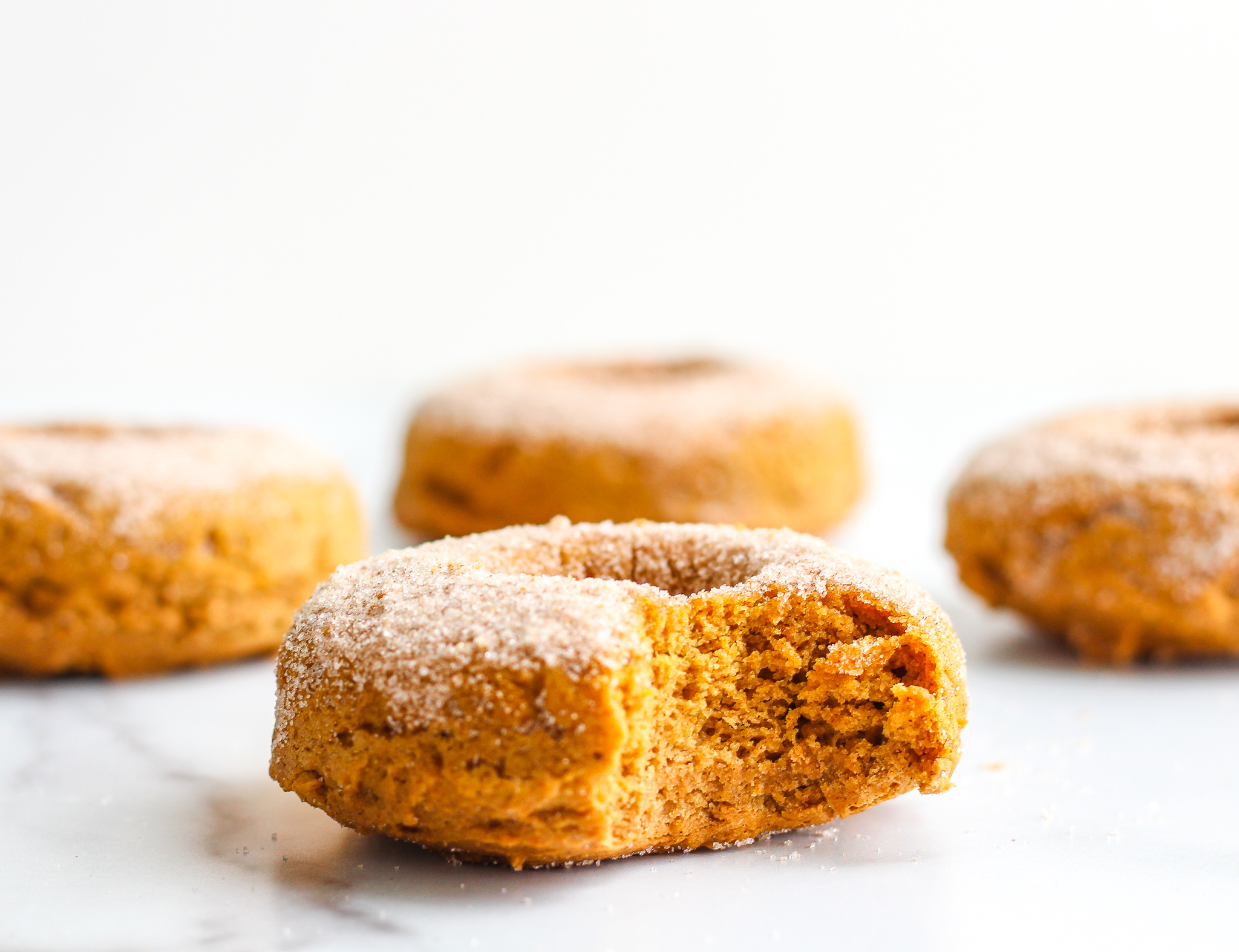 Gluten Free Pumpkin Spiced Donut with a bite taken out of it