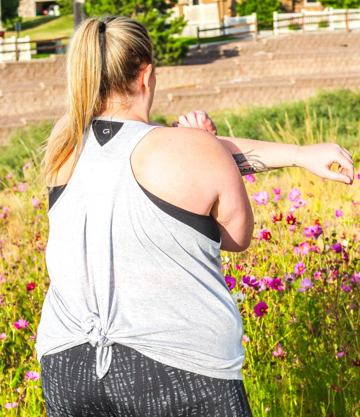 Plus size woman in workout gear stretching outside
