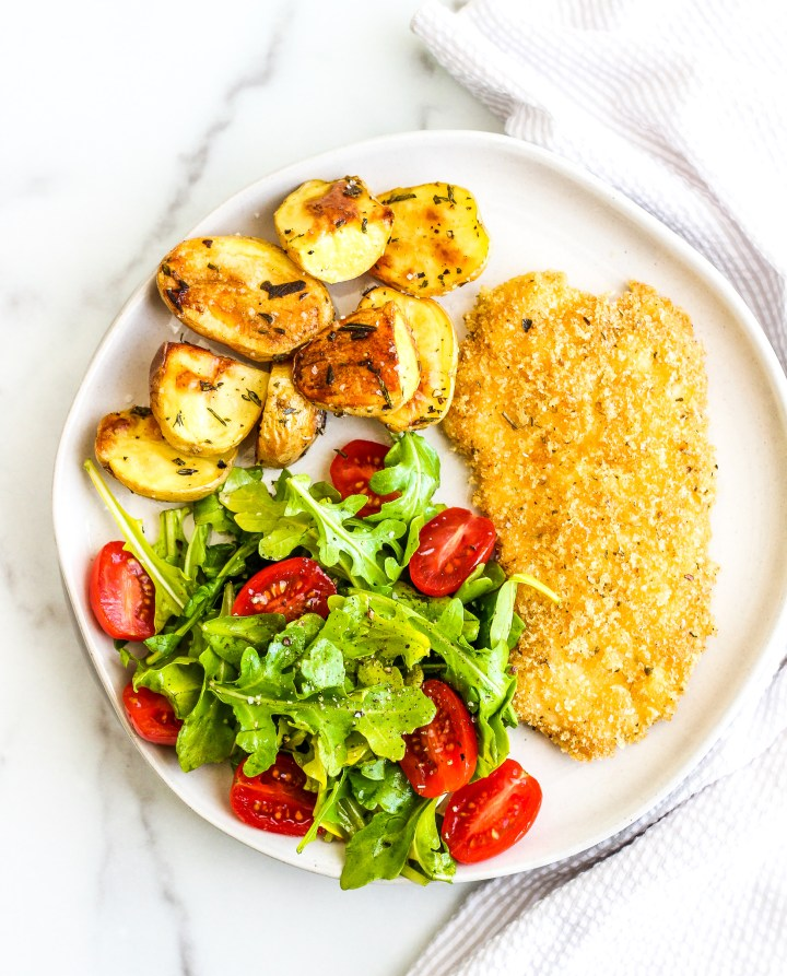 crispy chicken cutlet on a white serving plate with a side salad and roasted potatoes
