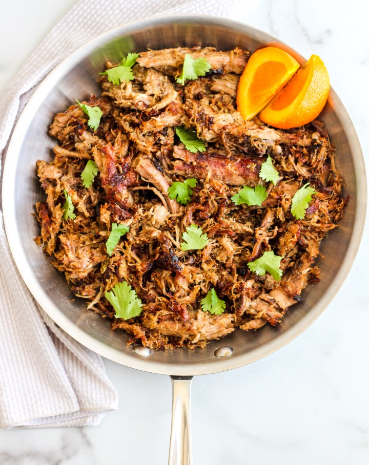 Crispy pork carnitas in a skillet topped with cilantro and a side of orange slices