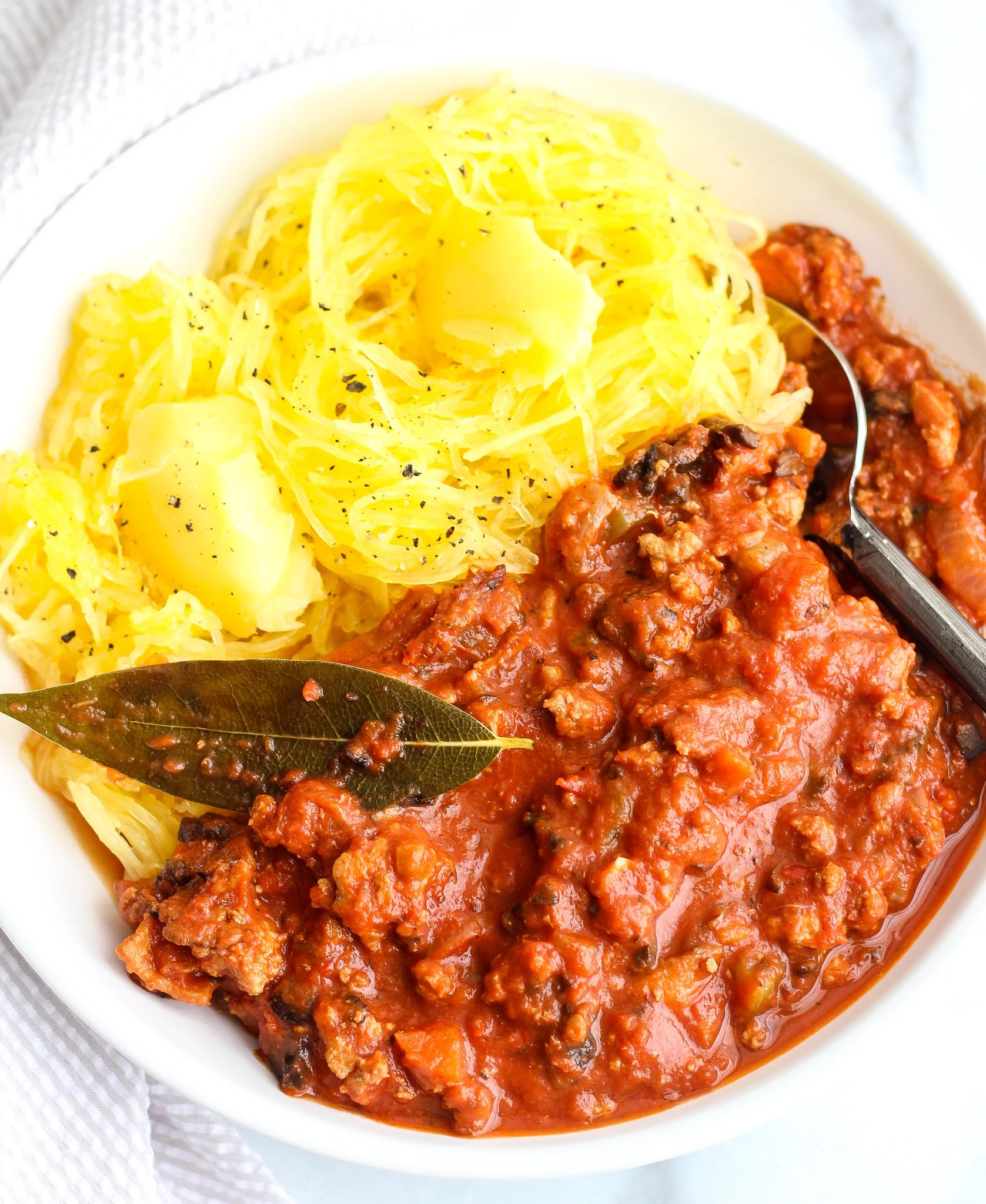 Whole30 Turkey Bolognese in a white bowl with swirled spaghetti squash topped with ghee