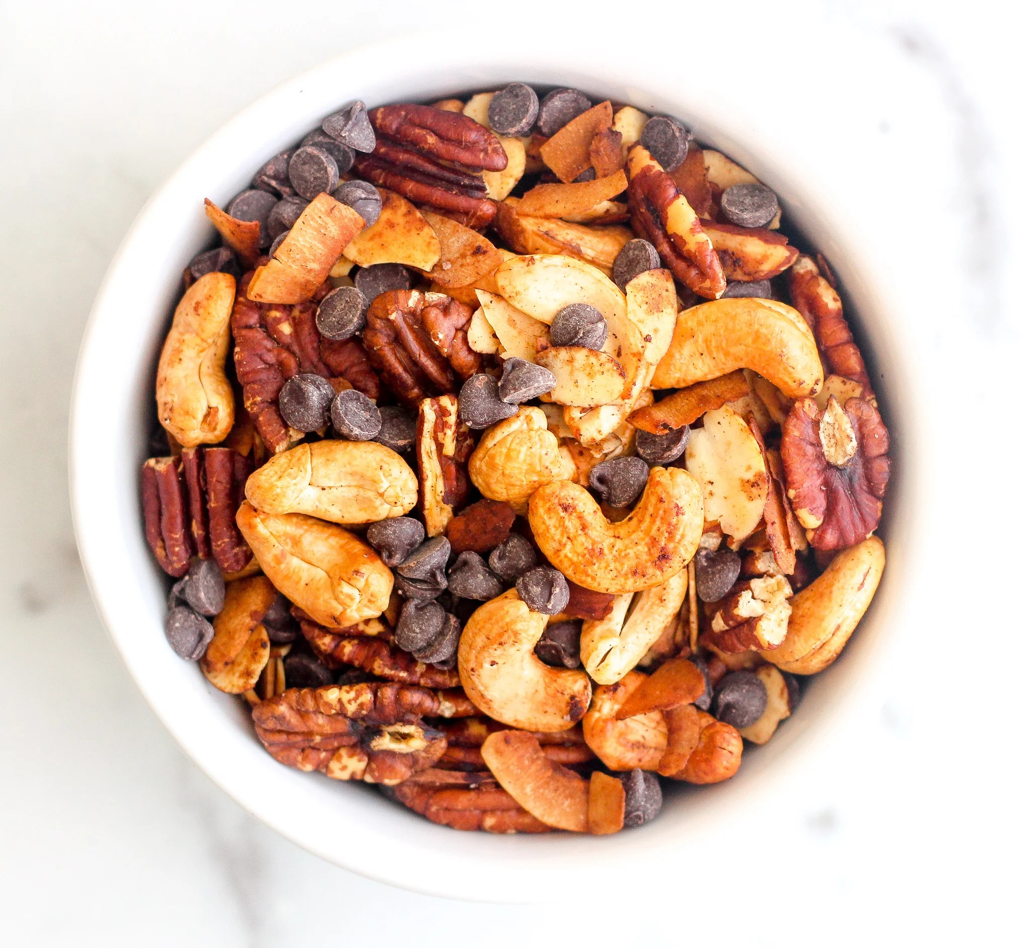 Keto trail mix in a white bowl with cashews, almonds, pecans, coconut flakes and sugar free chocolate chips