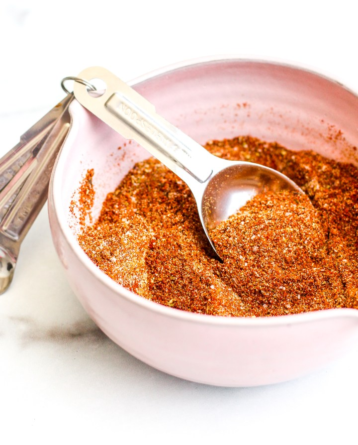 Homemade taco seasoning in a pick ceramic bowl with a silver measuring spoon inside
