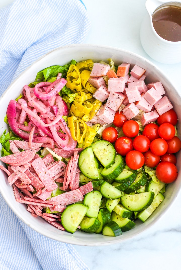 Italian chopped salad in a large ceramic bowl with layers of cherry tomatoes, cubed ham, chopped salami, chopped cucumbers, onions and lettuce