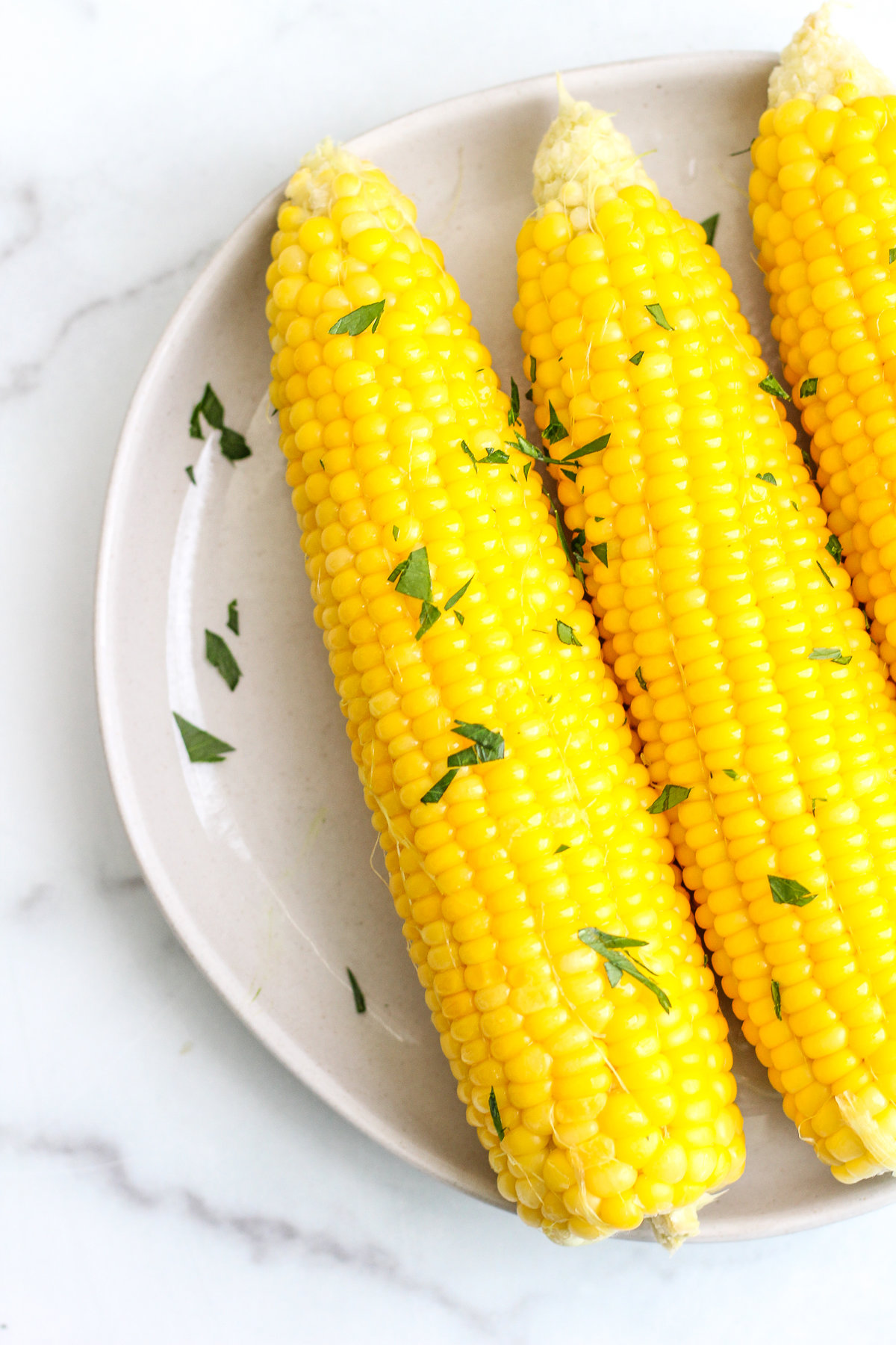 Bright yellow corn on the cob topped with butter and parsley on a plate