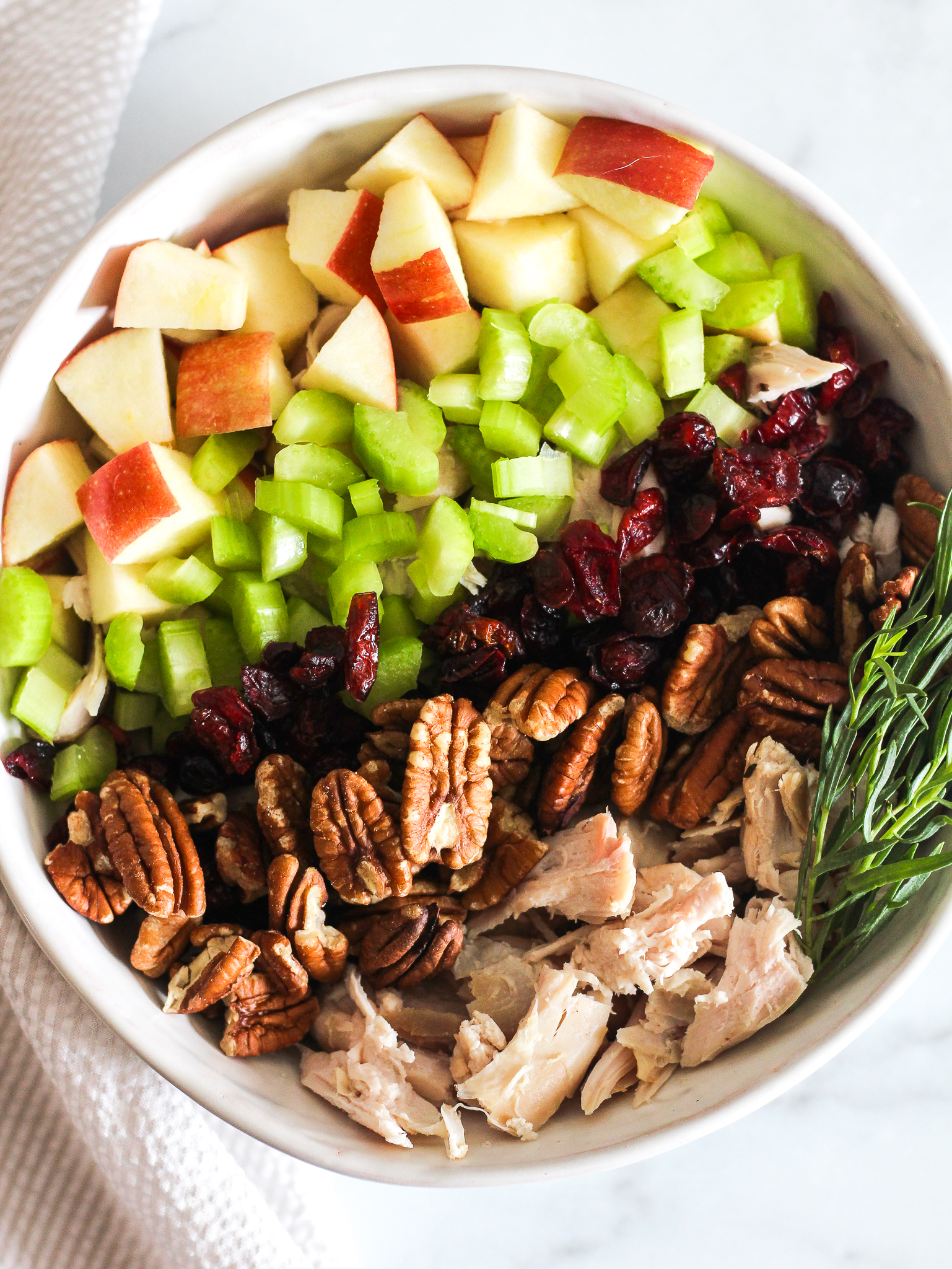 layers of apples, celery, cranberries, pecans, chicken and some tarragon in a white bowl