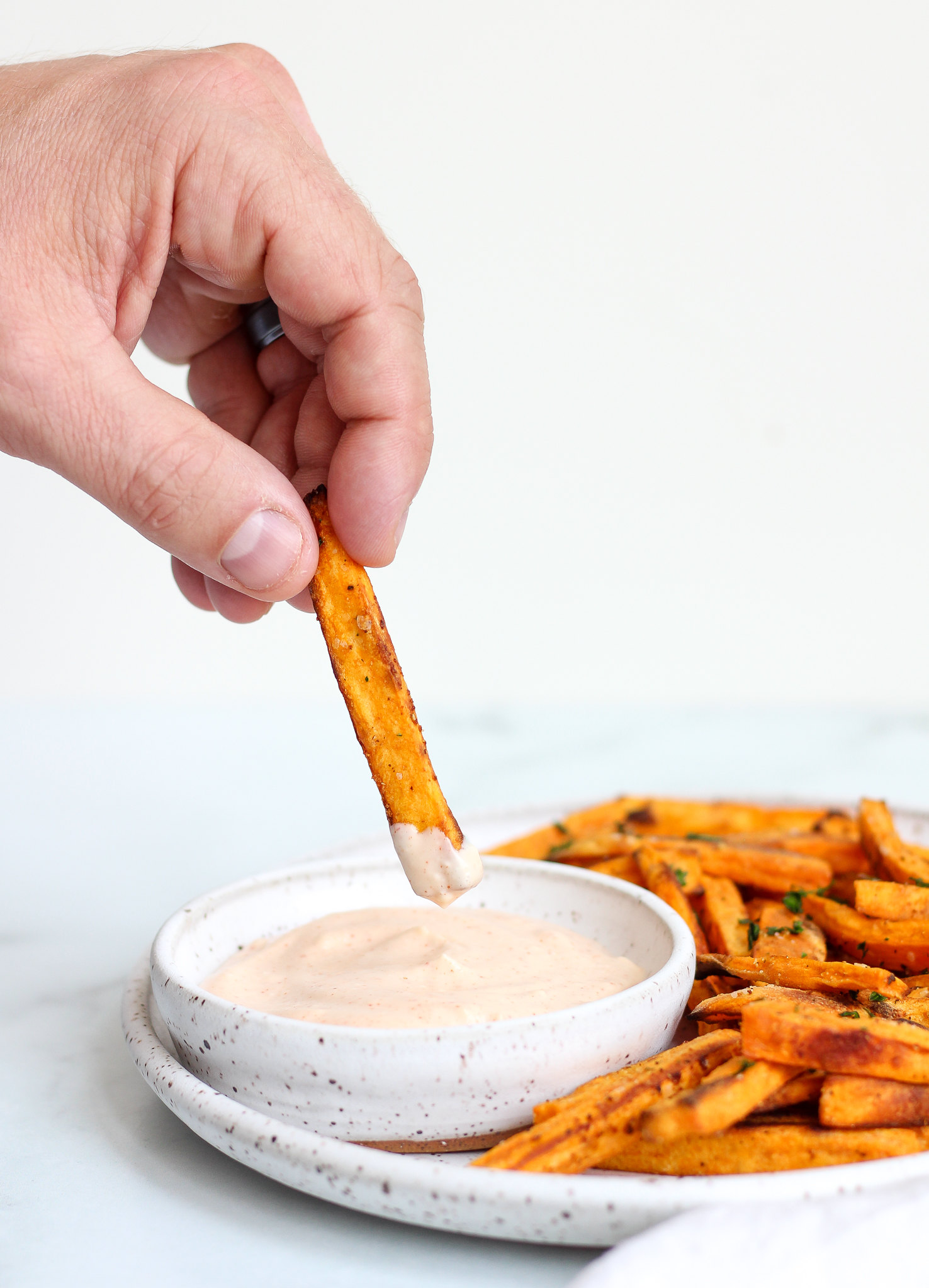 hand dipping an oven baked sweet potato fry into a spicy garlic aioli