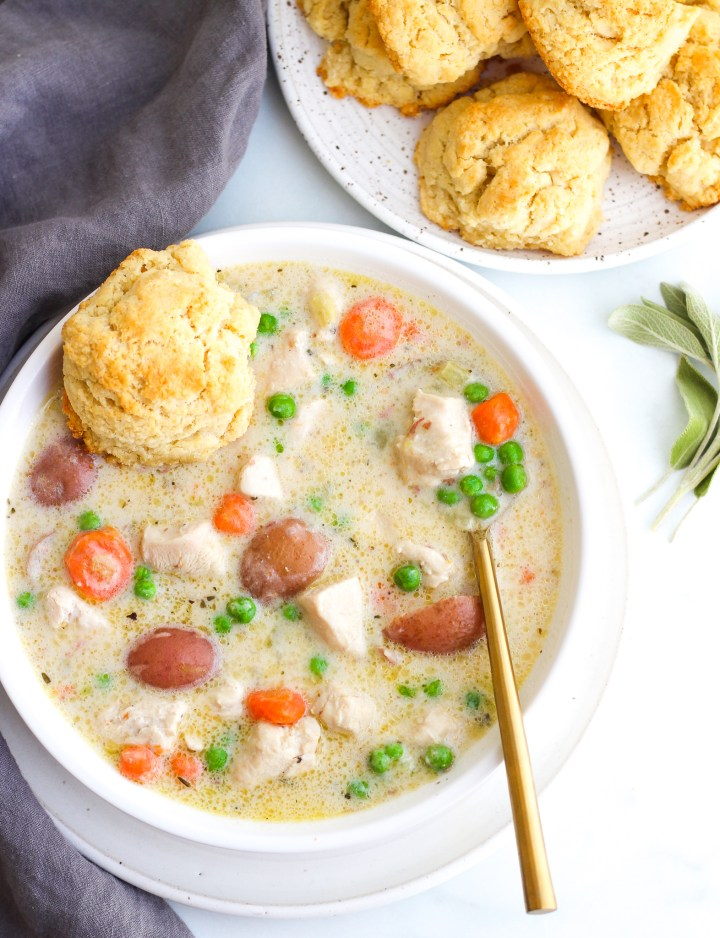 Chicken Pot Pie Soup in a white serving bowl, topped with a fresh biscuit