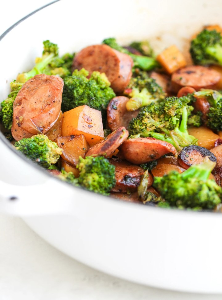 Broccoli, potatoes and chicken sausage in a large white skillet