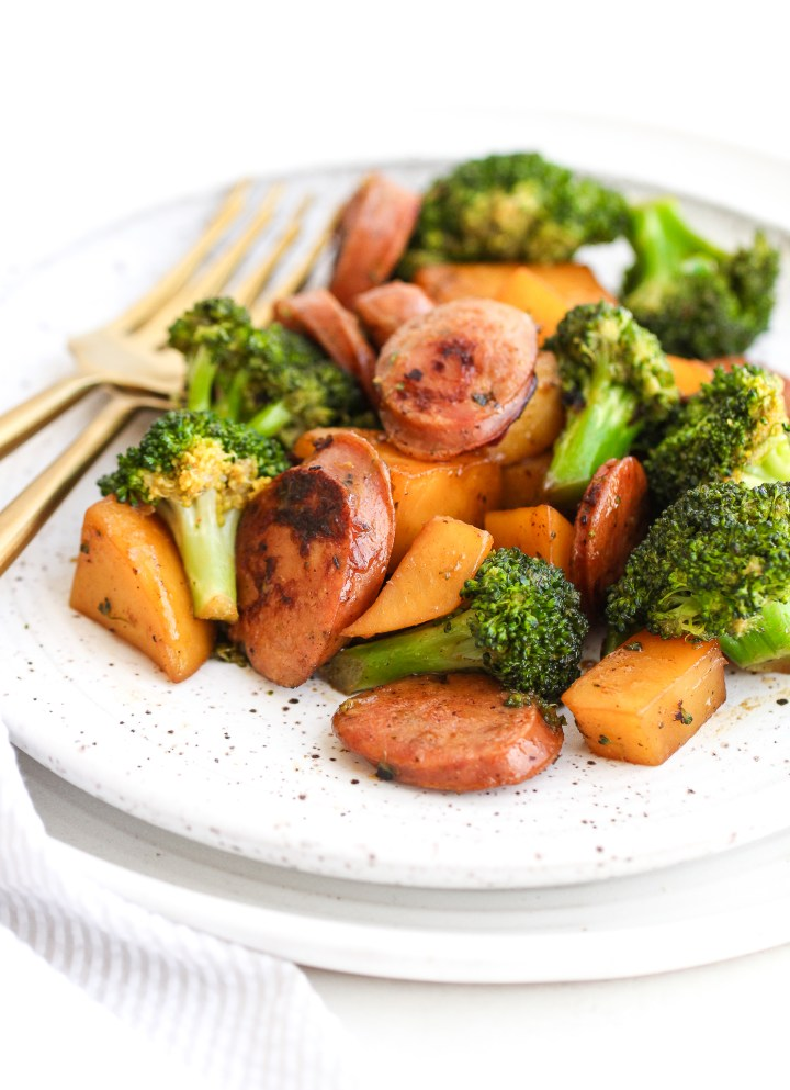 Broccoli, potatoes and chicken sausage on a ceramic plate with gold forks next to it