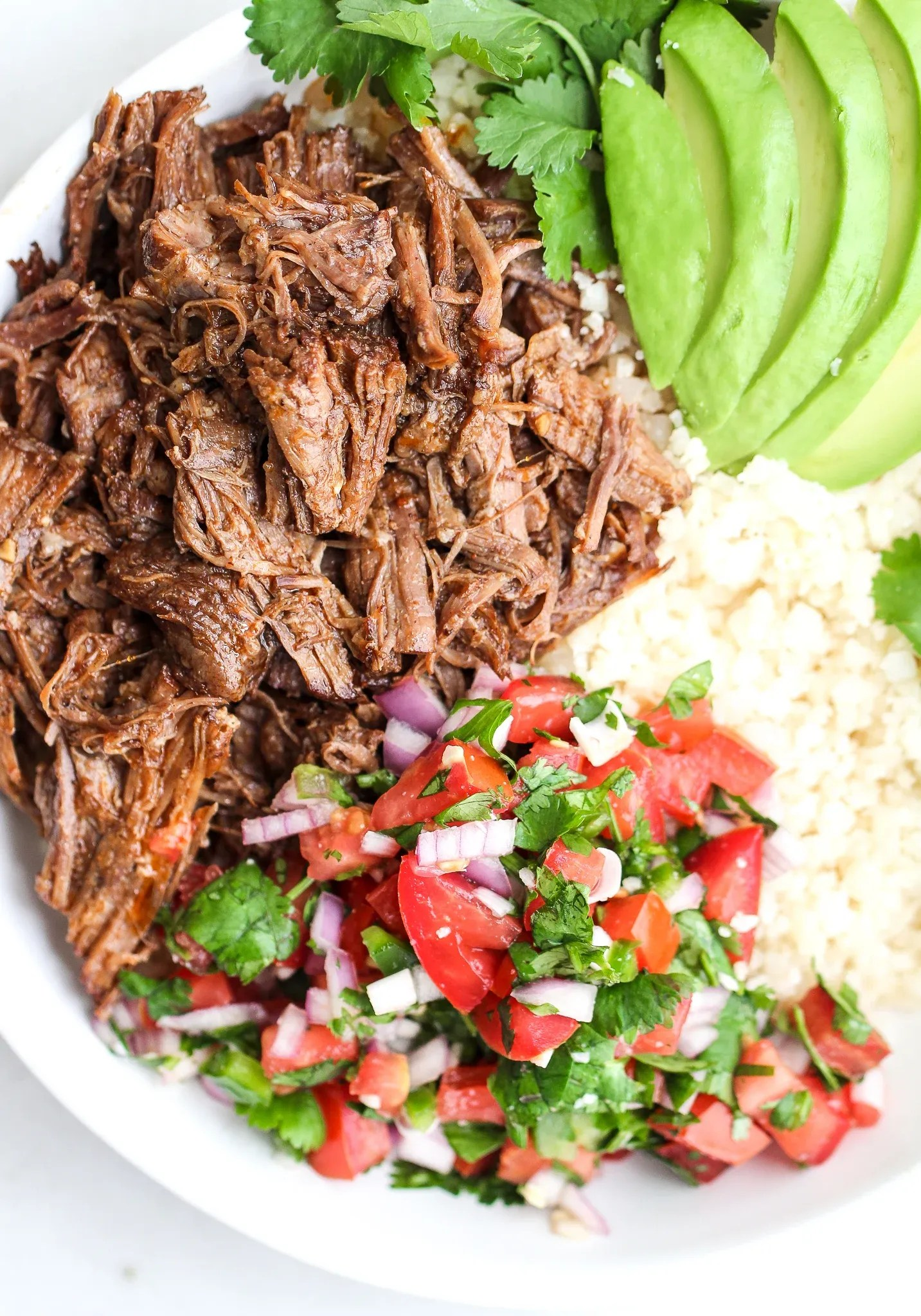 Mexican shredded beef in a white bowl with fresh salsa and sliced avocado
