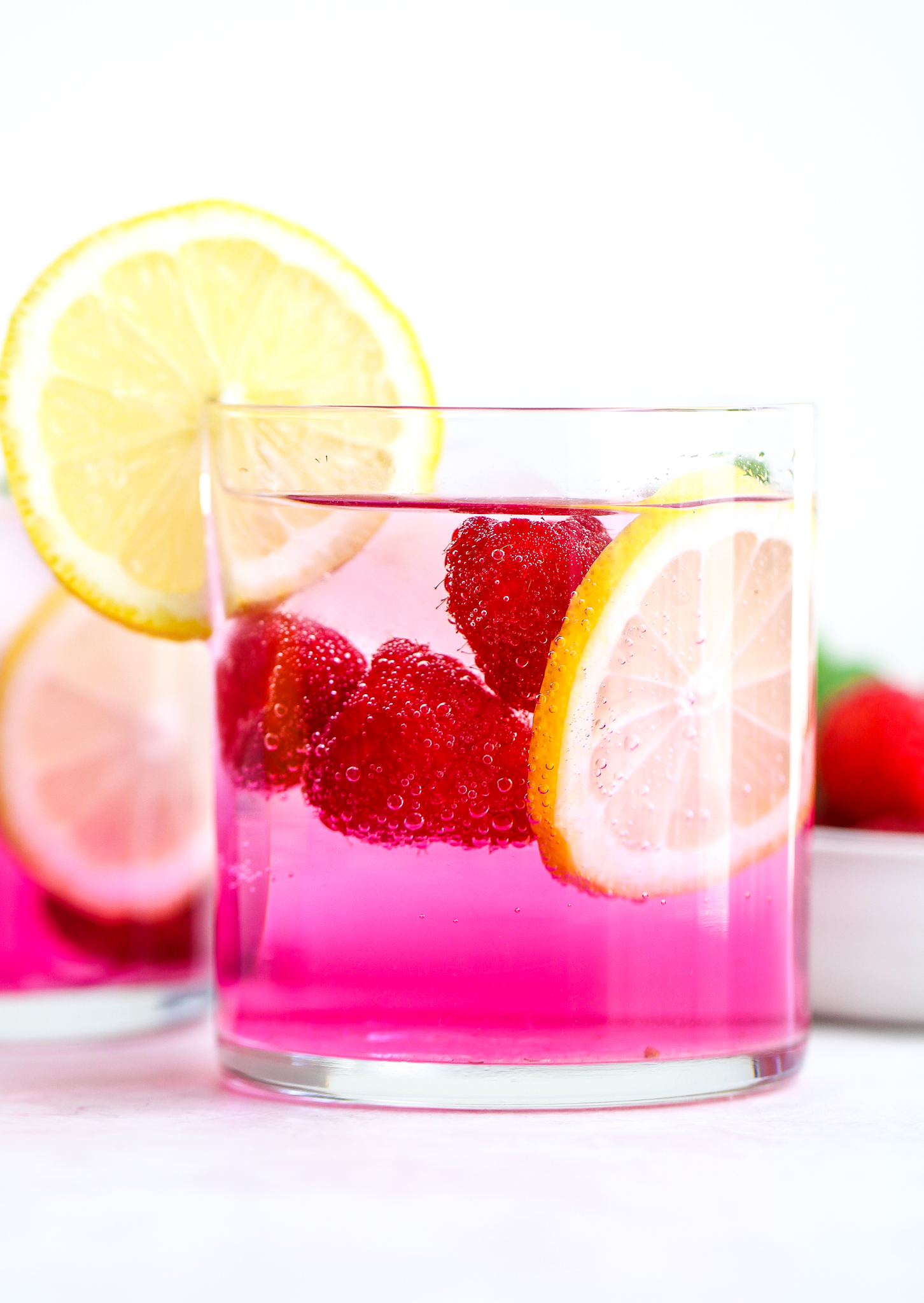clear cocktail glass filled with pink electrolyte drink, fresh raspberries, sliced lemon and an ice cube