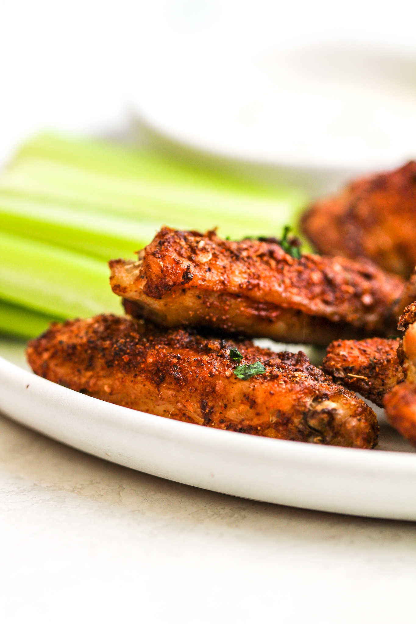 up close photo of crispy dry rub chicken wings on a white plate