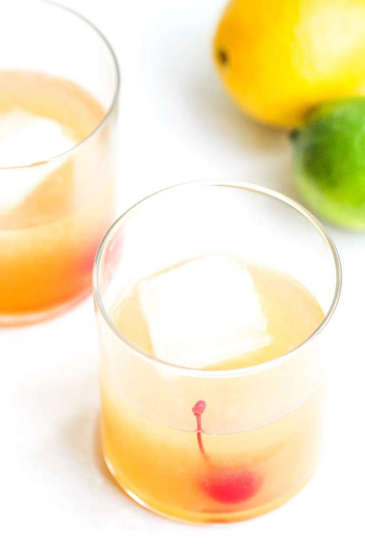 overhead shot of a classic whiskey sour in a clear cocktail glass. You can see a large ice cube and maraschino cherry inside - lemons and limes sit in the background