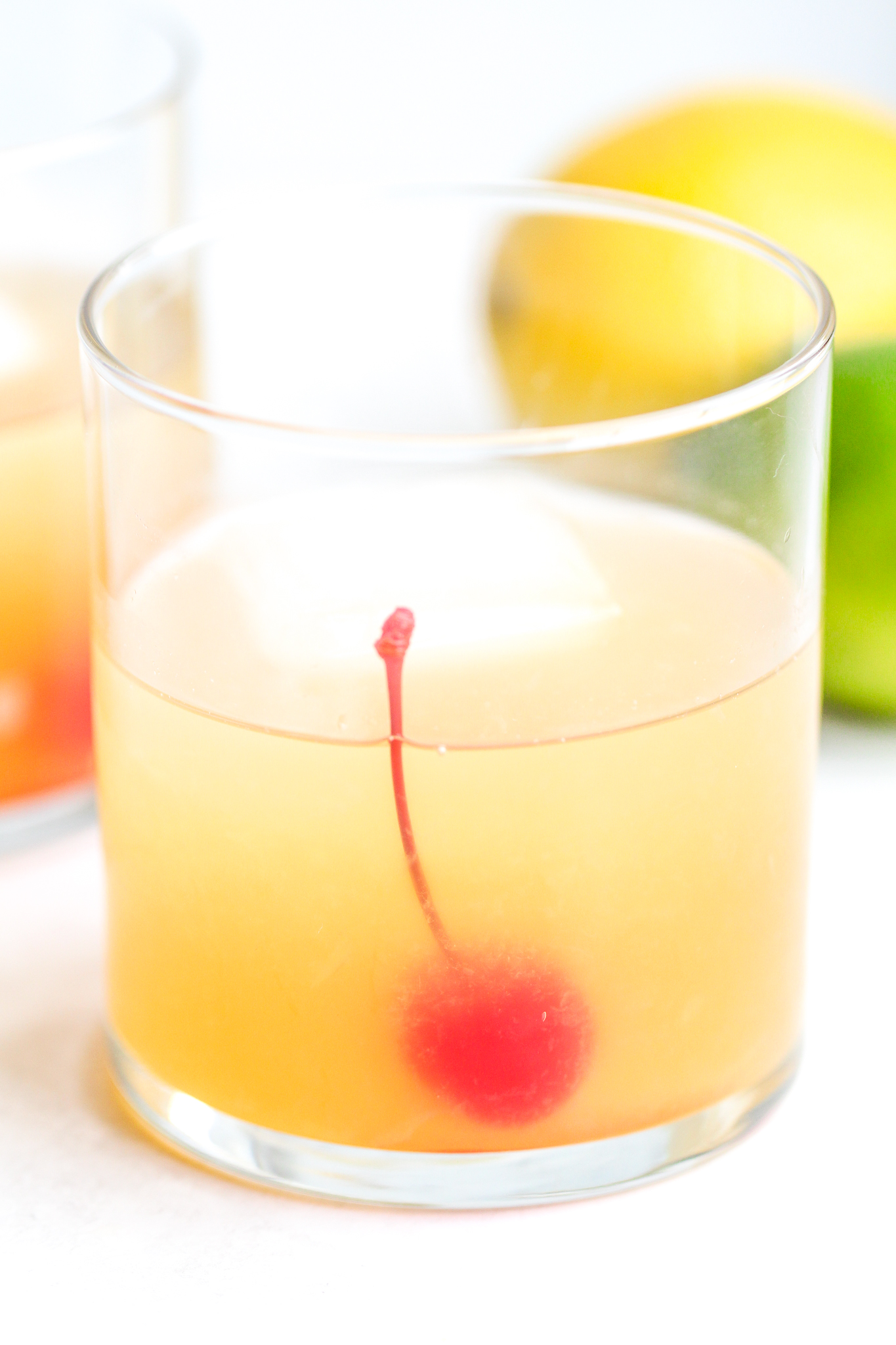 clear cocktail glass filled with a classic whiskey sour and a maraschino cherry inside