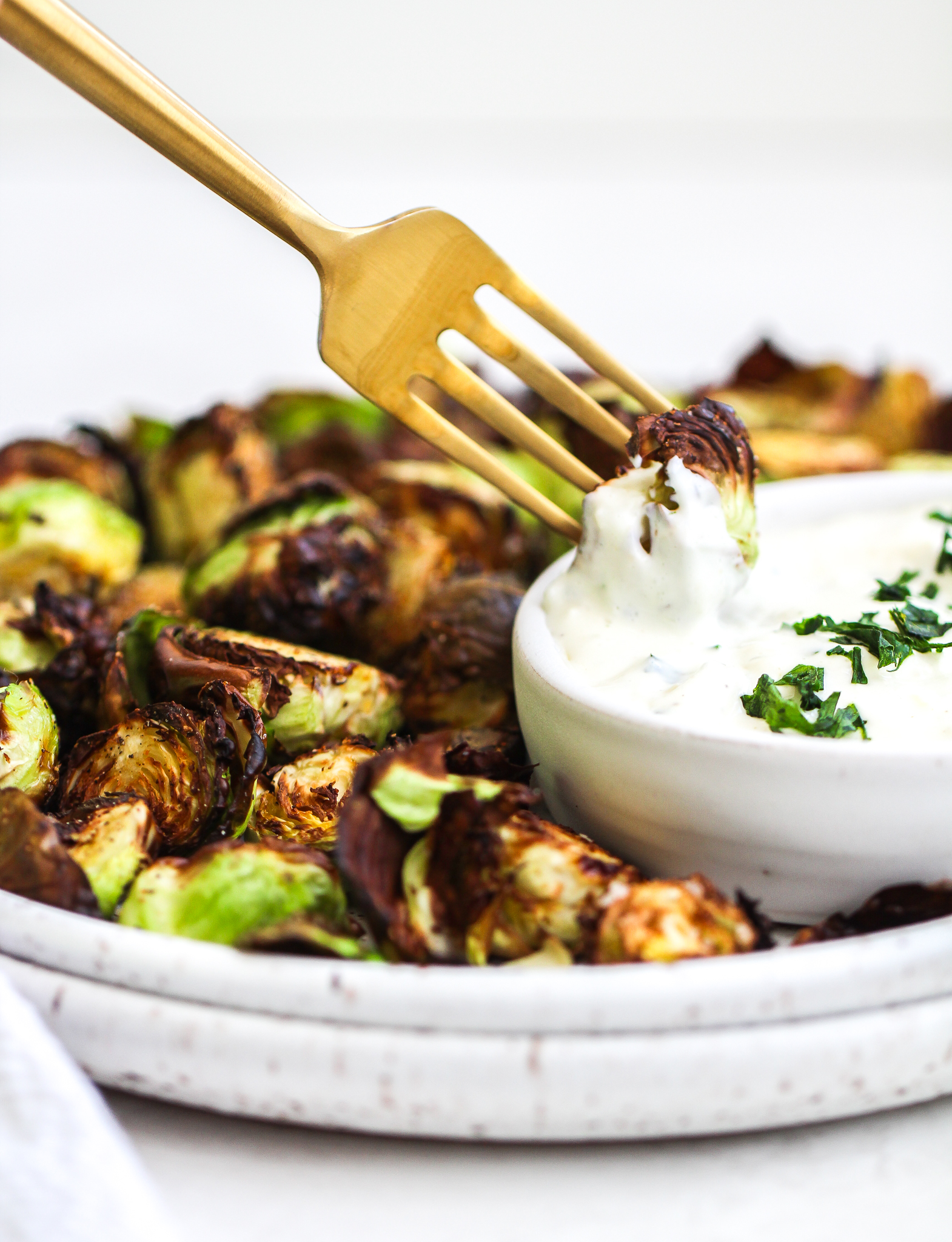 matte gold fork dipping a crispy air fryer Brussels sprout in lemon garlic aioli