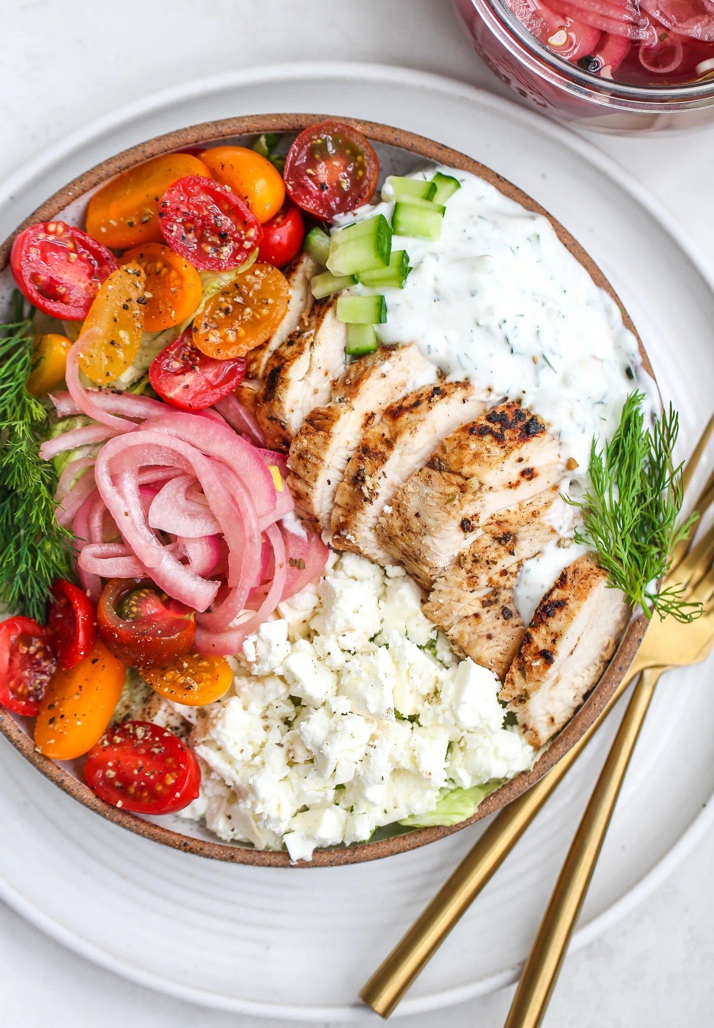 Healthy Greek chicken salad with fresh tomatoes, cucumbers, dill, tzatziki, feta and pickled onions