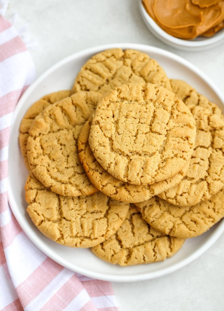 gluten free peanut butter cookies on a white ceramic plate next to a pink and white tea towel with a small bowl of peanut butter in the background