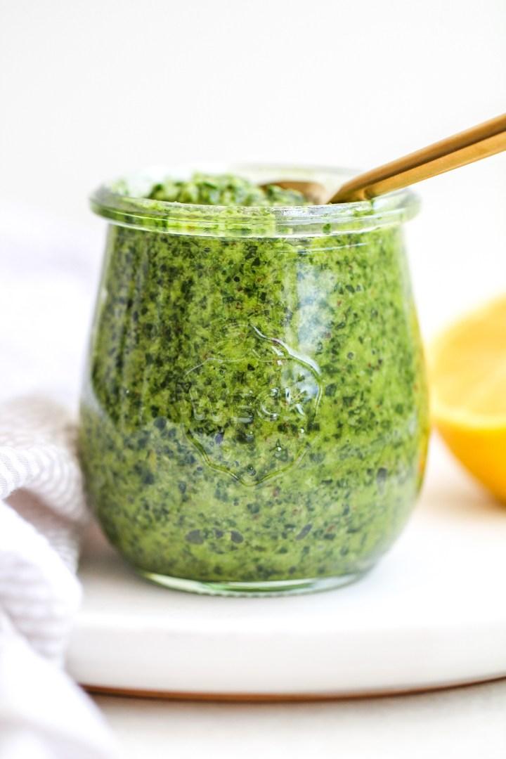 side shot of spinach, arugula & walnut pesto in a small glass jar