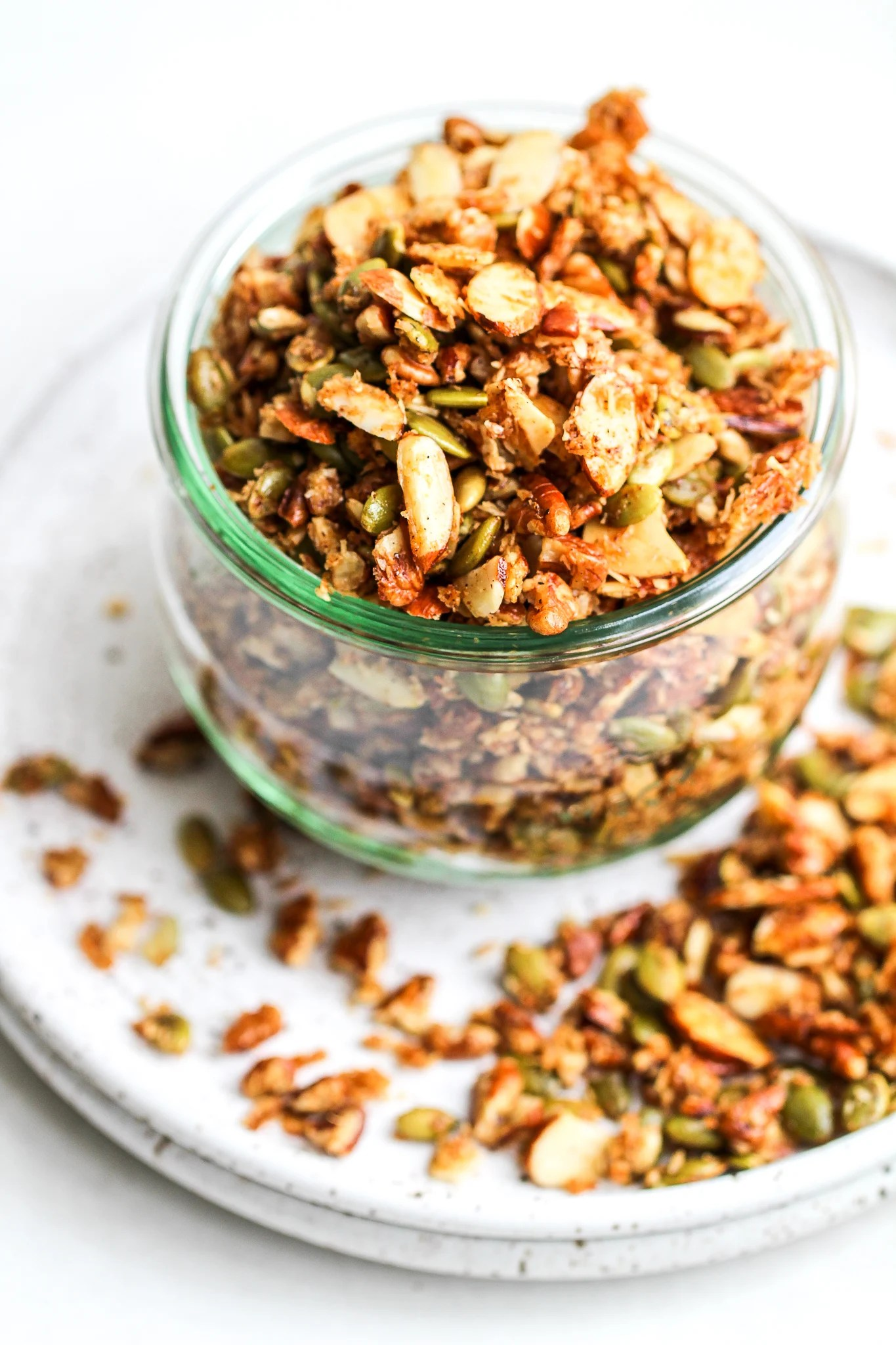 paleo granola in a glass jar overflowing onto a ceramic plate