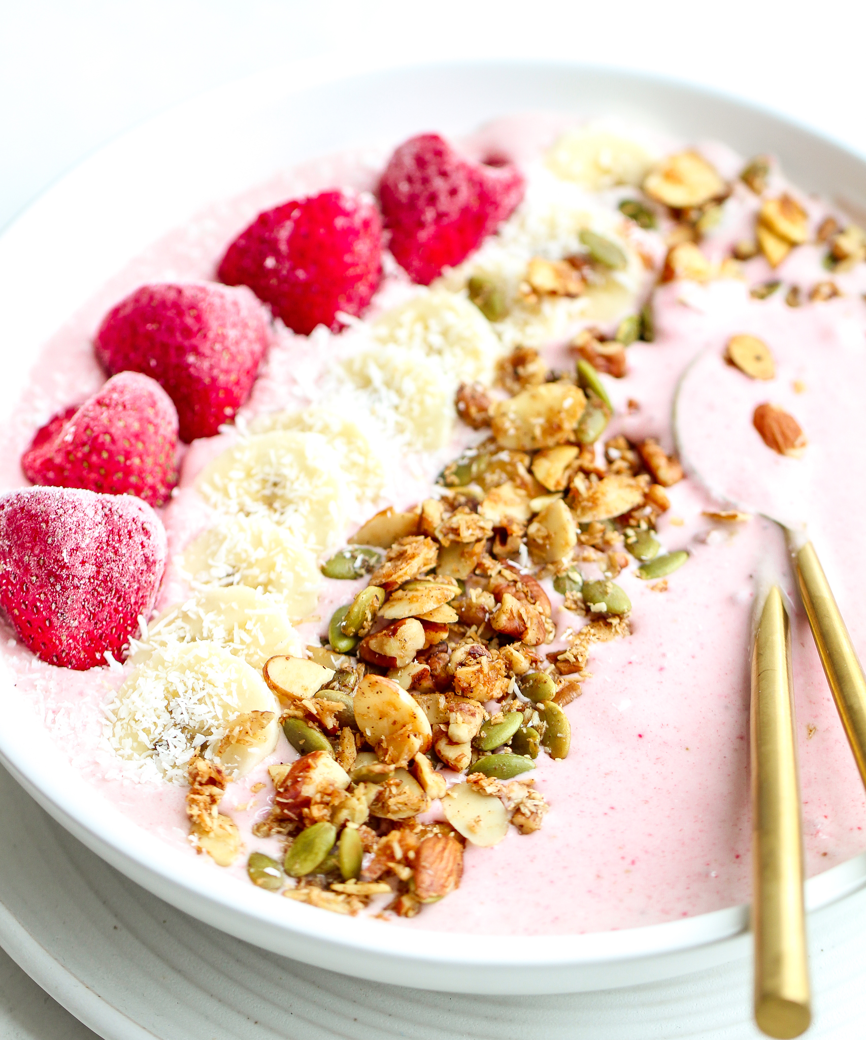 strawberry banana smoothie in a white bowl, topped with strawberries, sliced bananas, homemade granola and shredded coconut. There are matte golden spoons in the smoothie bowl